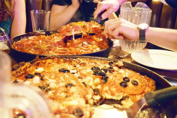 People eating in restaurant Chicago deep dish pizza